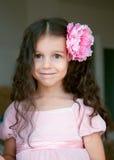 Niña feliz con la flor rosada grande en pelo Imagenes de archivo