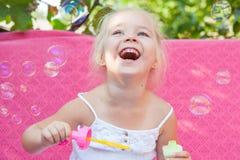 Niña feliz con las burbujas de jabón Foto de archivo