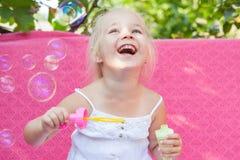 Niña feliz con las burbujas de jabón Foto de archivo libre de regalías