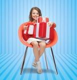 Niña feliz con las cajas de regalo que se sientan en silla Fotografía de archivo libre de regalías
