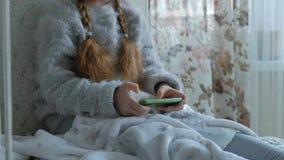 Niña feliz con las coletas en los auriculares, aplicaciones el teléfono, juegos, sonrisa, sentándose en el cuarto en el alféizar almacen de metraje de vídeo