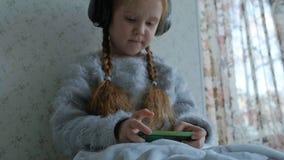 Niña feliz con las coletas en los auriculares, aplicaciones el teléfono, juegos, sonrisa, sentándose en el cuarto en el alféizar metrajes