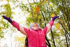 Niña feliz con las manos para arriba en parque del otoño Foto de archivo