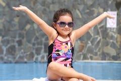 Niña feliz con los brazos abiertos fuera de la piscina Foto de archivo libre de regalías