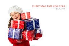 Niña feliz con los regalos de la Navidad en fondo blanco aislado Imagen de archivo libre de regalías