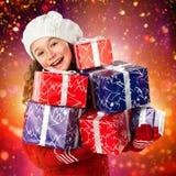 Niña feliz con los regalos de la Navidad en fondo de las luces Foto de archivo