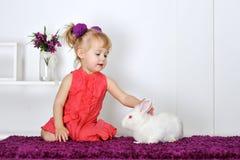 Niña feliz con un pequeño conejo blanco Foto de archivo