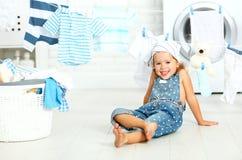 Niña feliz de la diversión del niño para lavar la ropa y risas en laund foto de archivo libre de regalías