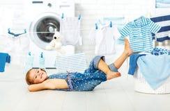 Niña feliz de la diversión del niño para lavar la ropa y risas en laund imágenes de archivo libres de regalías