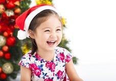Niña feliz delante del árbol de navidad Fotos de archivo