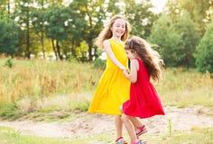 Niña feliz dos que abraza y que baila en el día de verano soleado Fotografía de archivo