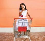 Niña feliz en carro de la compra con helado sabroso Imagen de archivo libre de regalías