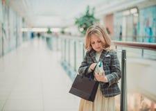 Niña feliz en carro de la compra y sus padres que disfrutan de fin de semana en centro comercial grande imagen de archivo