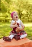 Niña feliz en el casquillo que juega con el oso de peluche Imagen de archivo