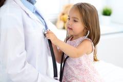 Niña feliz en el examen de la salud en la oficina del doctor Concepto de la medicina y de la atención sanitaria imagen de archivo