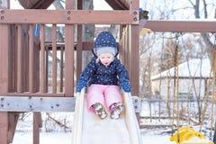 Niña feliz en el mono de nieve que va abajo de la diapositiva Fotos de archivo libres de regalías