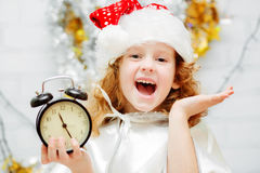 Niña feliz en el sombrero de Papá Noel que sostiene un reloj en sus manos Chr Imagen de archivo