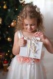 Niña feliz en el vestido blanco que sostiene una caja con un regalo Imagen de archivo