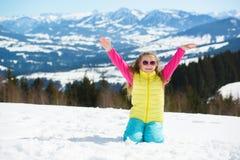 Niña feliz en gafas de sol en montañas del invierno en un día soleado Fotografía de archivo