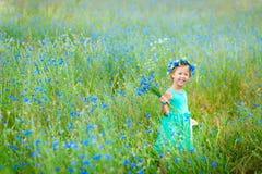 Niña feliz en un campo que sostiene un ramo de flores azules Imágenes de archivo libres de regalías