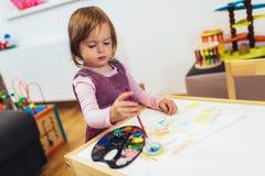 Niña feliz linda, preescolar, pintando con color de agua foto de archivo libre de regalías