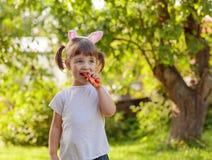 Niña feliz que come la zanahoria fresca y dulce imagen de archivo libre de regalías