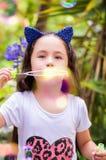 Niña feliz que juega con las burbujas de jabón en una naturaleza del verano, accesorios del azul que llevan de un tigre de los oí Imagen de archivo