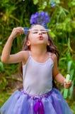 Niña feliz que juega con las burbujas de jabón en una naturaleza del verano, accesorios del azul que llevan de un tigre de los oí Foto de archivo libre de regalías