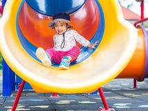 Niña feliz que juega el resbalador en el patio Niños, ha foto de archivo