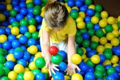 Niña feliz que juega en el patio plástico colorido de las bolas Foto de archivo libre de regalías