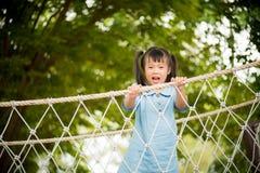 Niña feliz que juega subir en el puente de cuerda imagen de archivo