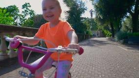 Niña feliz que monta una bici rosada almacen de metraje de vídeo