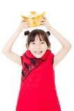 Niña feliz que muestra el oro por Año Nuevo chino Fotografía de archivo