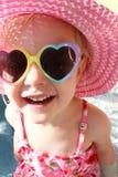 Niña feliz que ríe en traje de baño, el sombrero de Sun y gafas de sol imagen de archivo libre de regalías