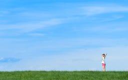 Niña feliz que se coloca en un campo en fondo del cielo azul Imagen de archivo