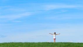 Niña feliz que se coloca en un campo en fondo del cielo azul Fotos de archivo