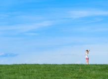 Niña feliz que se coloca en un campo en fondo del cielo azul Imagenes de archivo