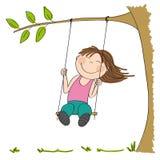 Niña feliz que se sienta en el oscilación, balanceando debajo del árbol Fotos de archivo libres de regalías