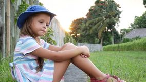 Niña feliz que se sienta en la hierba y que juega en jardín del verano outdoors Puesta del sol metrajes