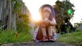 Niña feliz que se sienta en la hierba y que juega en jardín del verano outdoors Puesta del sol almacen de metraje de vídeo
