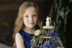 Niña feliz que sostiene la jaula de pájaros decorativa llena de flores Estudio tirado en interior del estilo de Provence Imagen de archivo libre de regalías