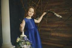 Niña feliz que sostiene la jaula de pájaros decorativa llena de flores Estudio tirado en interior del estilo de Provence Fotografía de archivo