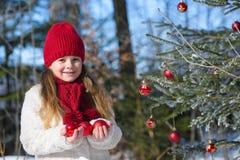 Niña feliz que sostiene las chucherías de la Navidad en el invierno f de las manos im Imagenes de archivo
