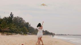 Niña feliz que vuela una cometa, corriendo alrededor de madre joven en la playa exótica durante la cámara lenta tropical de las v almacen de video