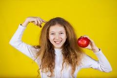 Niña feliz, sonriente que sostiene una manzana roja imagen de archivo libre de regalías