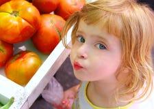 Niña hambrienta que gesticula en tomates del mercado Imagen de archivo