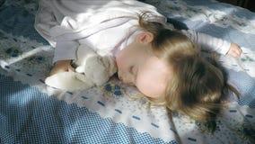 Niña hermosa con el pelo rubio que duerme en la cama y encendida por el sol, abrazando un conejito de la felpa metrajes