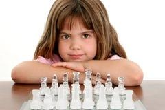 Niña hermosa con la tarjeta de ajedrez de cristal Foto de archivo libre de regalías
