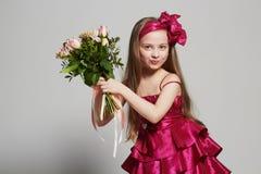 Niña hermosa con las flores niño feliz divertido Foto de archivo