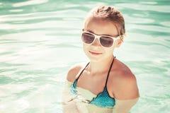 Niña hermosa con las gafas de sol en piscina al aire libre Foto de archivo